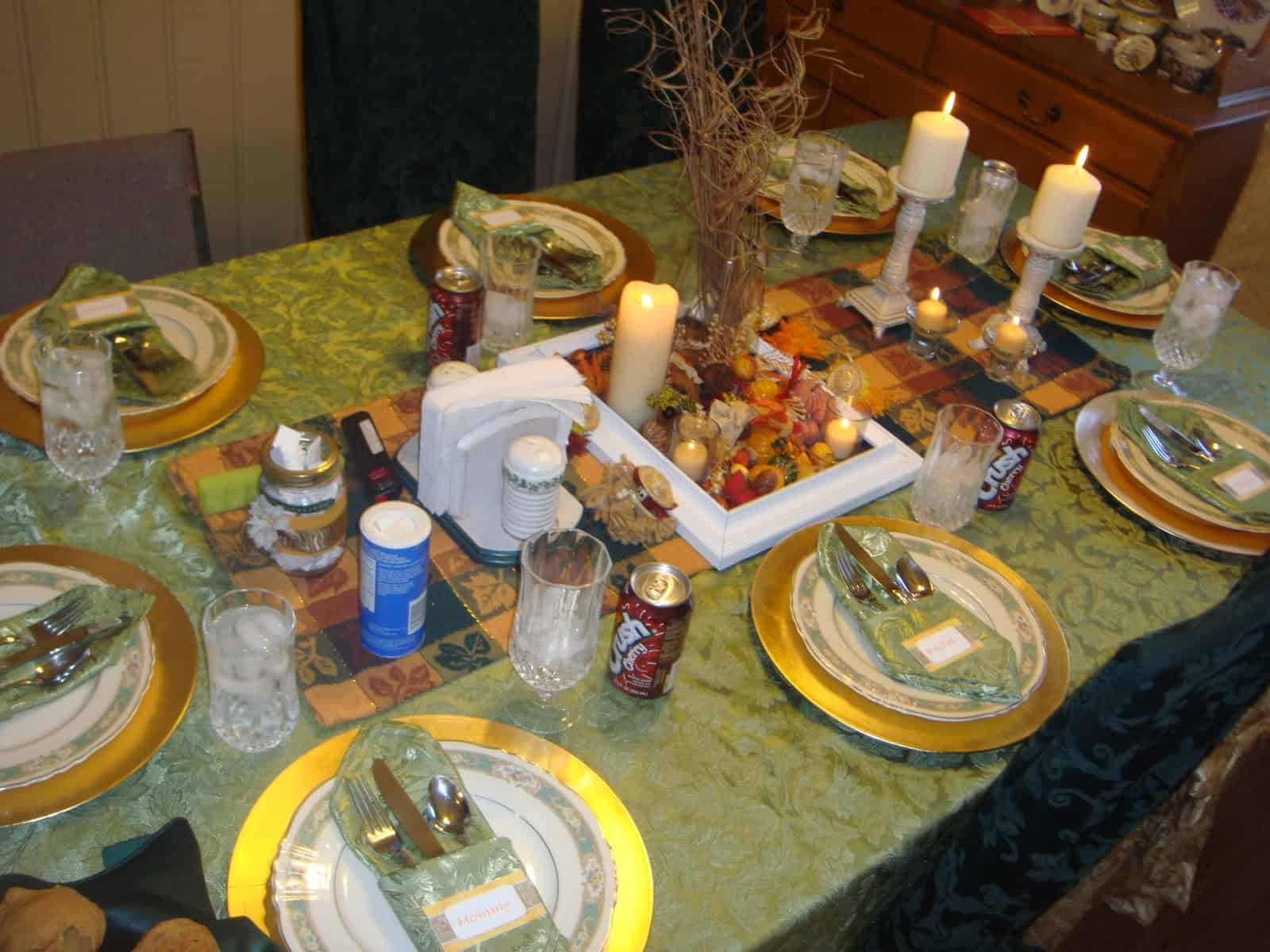 Table set with green tablecloth, gold chargers, fine china and crystal and Thanksgiving arrangement