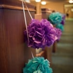 purple and teal paper pom poms on pews