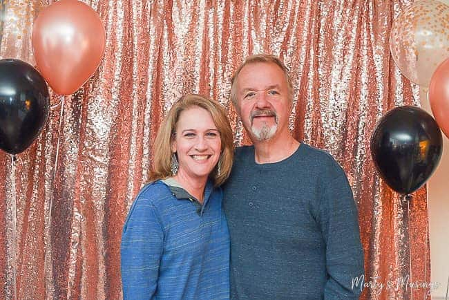 Husband and wife with pink and silver backdrop and black, clear and pink balloons