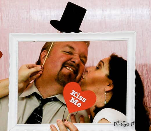 Husband and wife centered in empty frame with kiss me sign in photo booth