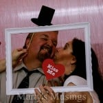 man with paper hat and woman with kiss me sign photographed inside white frame