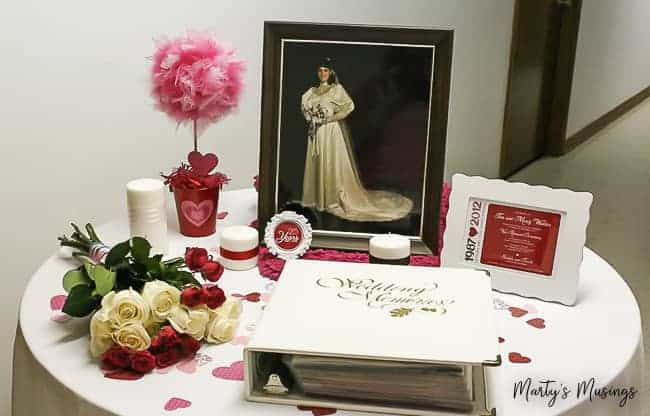 25th wedding anniversary reception table with wedding album and bridal portrait