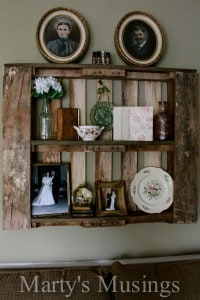 Old rustic pallet shelving hung on living room wall and decorated with vintage objects such as a plate, a vase, a weddding topper, a scrapbook and a globe.
