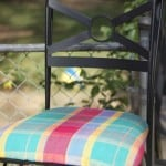 Black wrought iron chair with plaid green yellow and pink fabric
