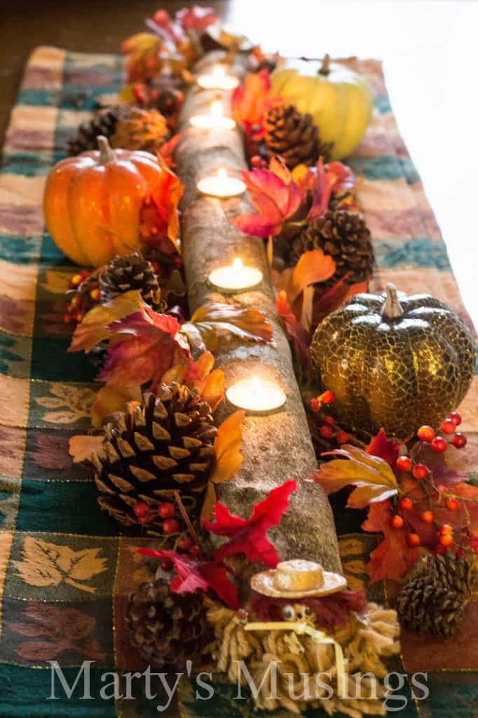 branch with holes cut out for tea candles and flowers, pinecones, acorns and fall decor arranged on top of table runner