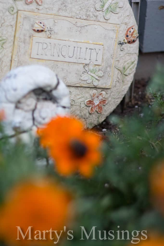 blurry foreground with ceramic round saying  of tranquility in a garden