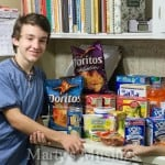 boy in blue shirt leaning against counter with groceries on it