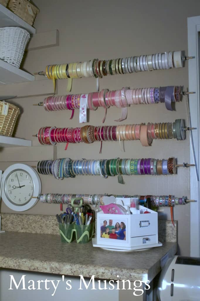 dowel rods with ribbons stored on craft room wall