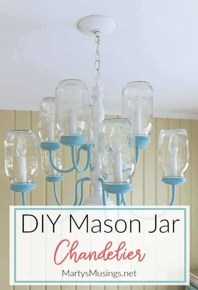 Have some extra mason jars and an outdated chandelier? Turn them into a clever DIY Mason Jar Chandelier! These mason jars are turned upside down and the chandelier chalk painted for a unique shabby chic look. #masonjars #repurposed #shabbychic #homedecor #fixerupper #DIY #rustic #martysmusings