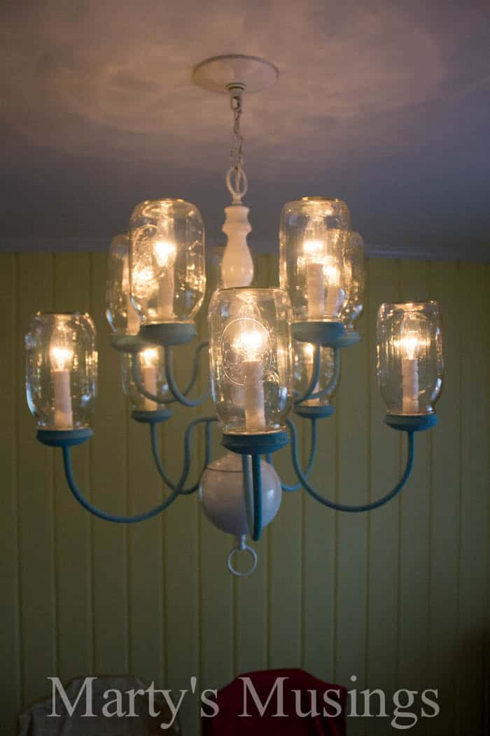Have some extra mason jars and an outdated chandelier? Turn them into a clever DIY Mason Jar Chandelier! These mason jars are turned upside down and the chandelier chalk painted for a unique shabby chic loo