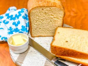 sliced homemade white bread with butter and blue napkin