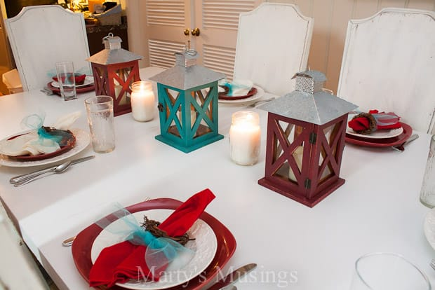 A beautiful rustic red and aqua tablescape set with lanterns and mix and match china and linens.