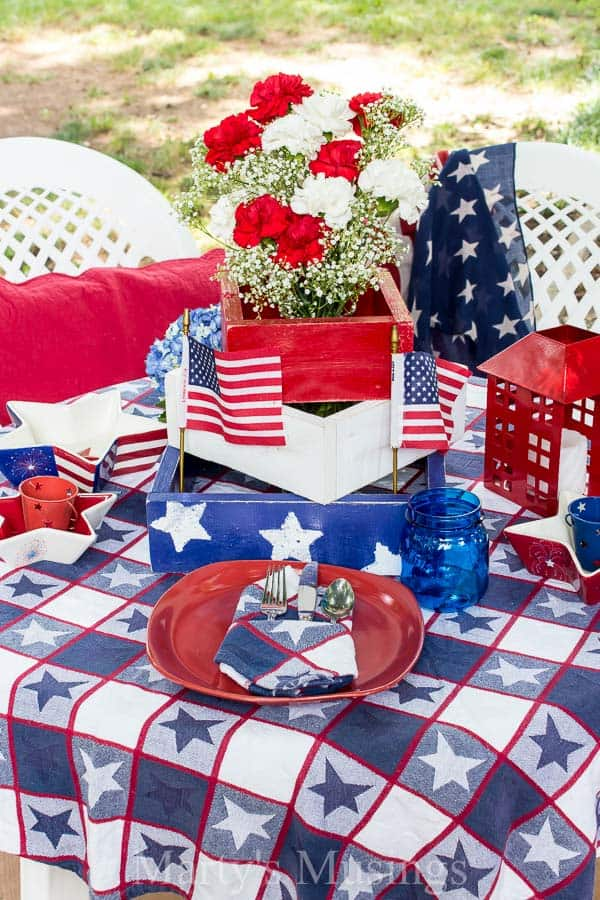 Red white and blue stars on tablecloth with red dishes and flowers