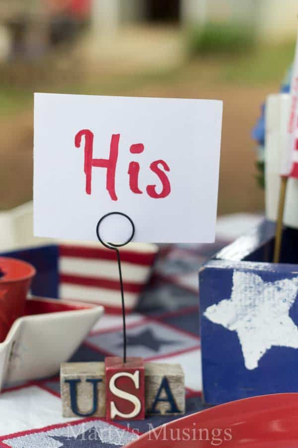 Inexpensive 4th of July table decorations from yard sales, thrift stores and around the home with seasonal flowers create a perfect rustic, outdoor setting.