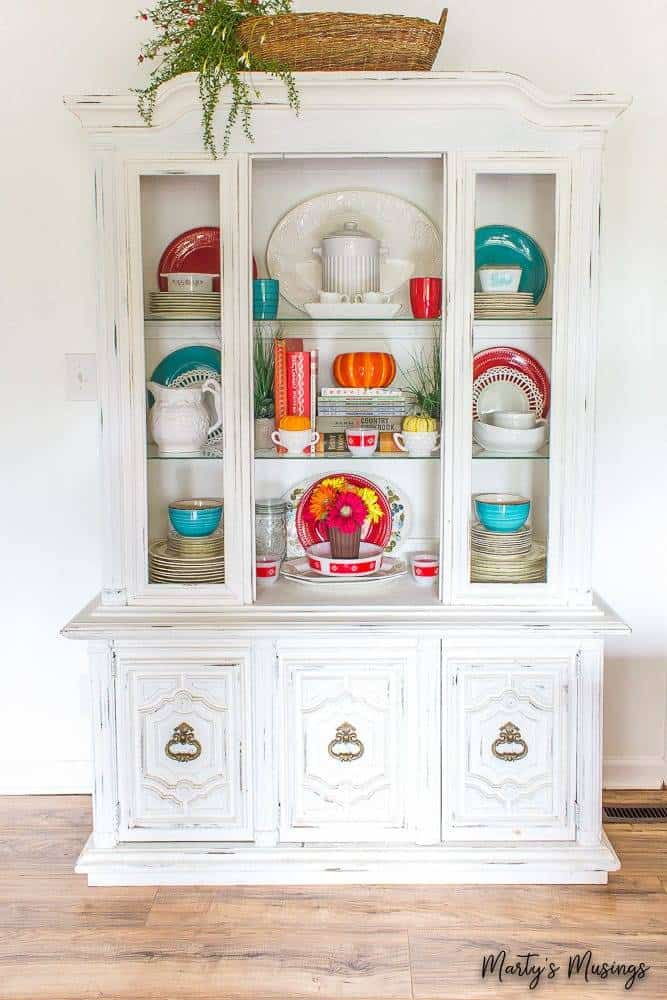 White china hutch decorated with orange and blue for fall
