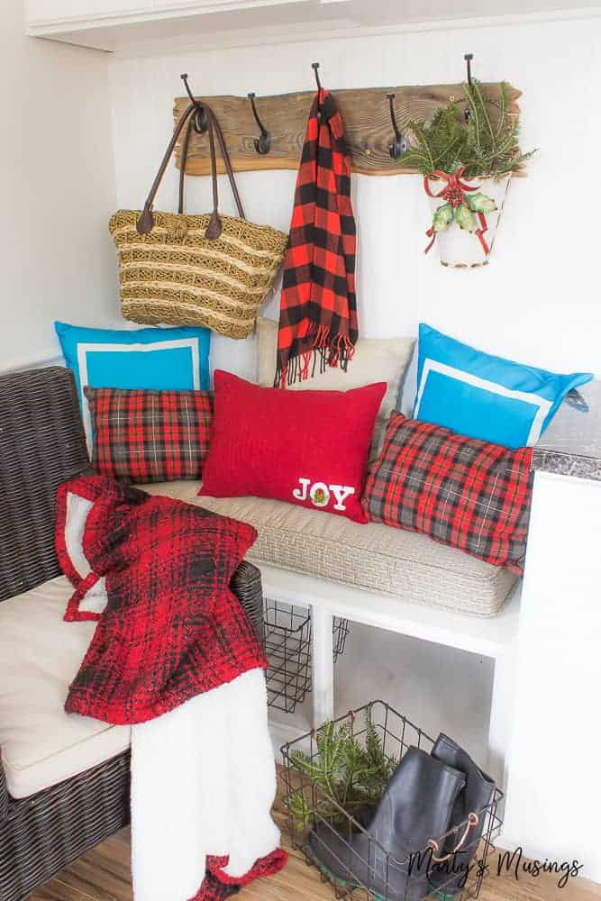 red and black buffalo plaid pillows and scarf on a bench