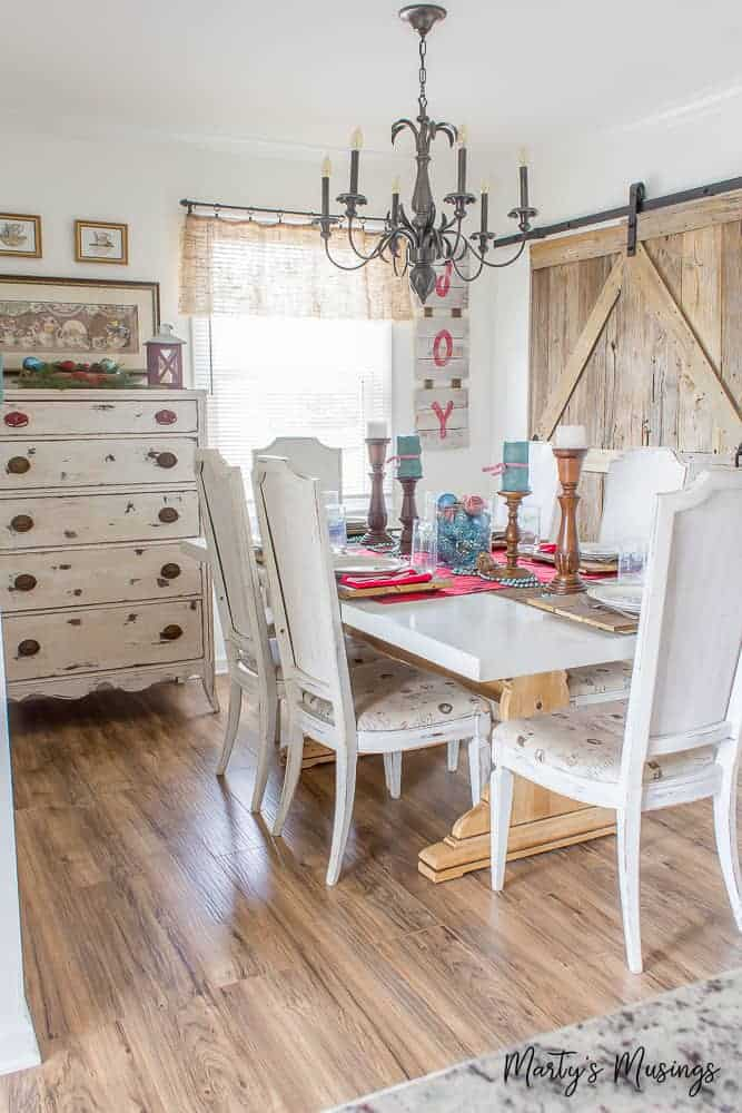 White farmhouse kitchen table with Christmas decorations and rustic barn door