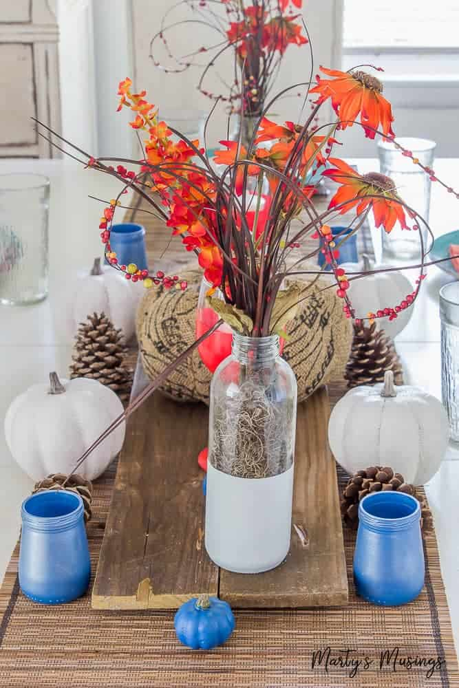 Take your fall decorating up a notch with these creative orange and blue fall table decorations. Includes a simple spray painting craft anyone can do!