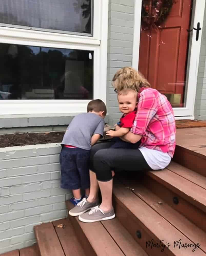 Grandmother helping her two grandsons outside front door of house