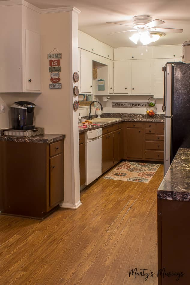 Brown bottom cabinets and white top cabinets in dated ranch style kitchen