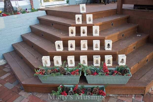 Create Christmas tree luminaries on your front deck or porch by using shaped luminaries and planters.