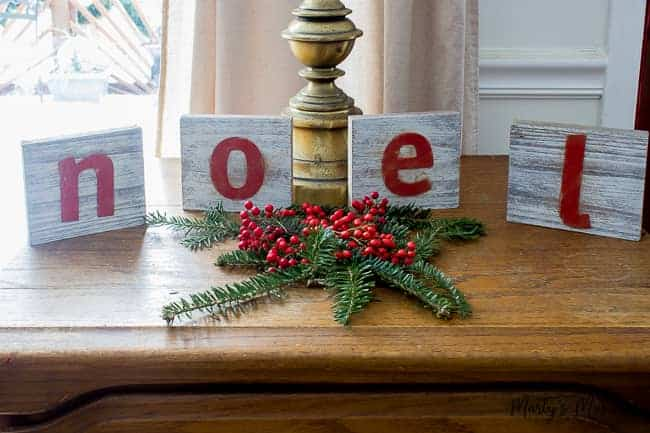 white washed wooden letters with noel on them and greenery and berries