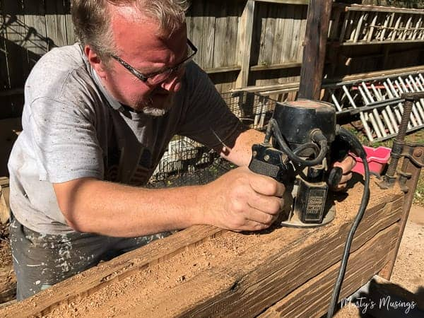 Man cutting out grooves in barn wood for mantel