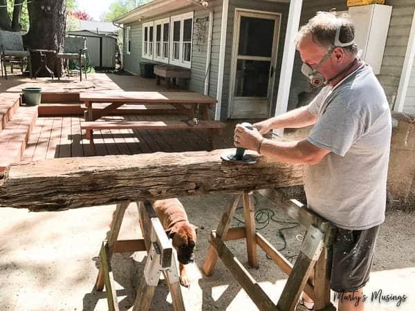 Man with mask sanding barn wood log