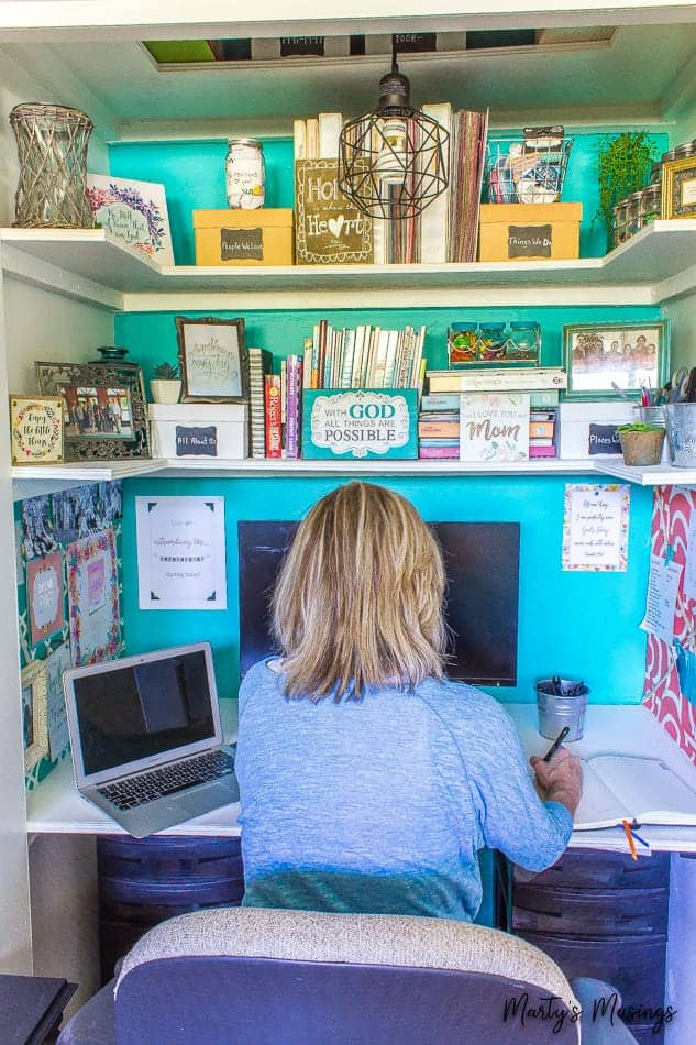 Home office in a closet with shelves and teal accent wall
