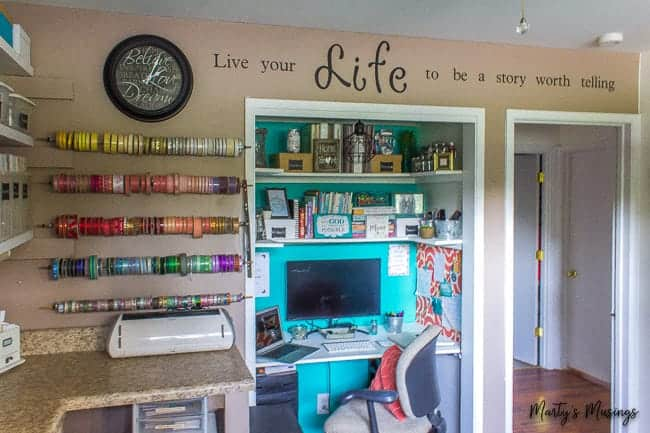 home office in a closet of a craft room with teal accent wall