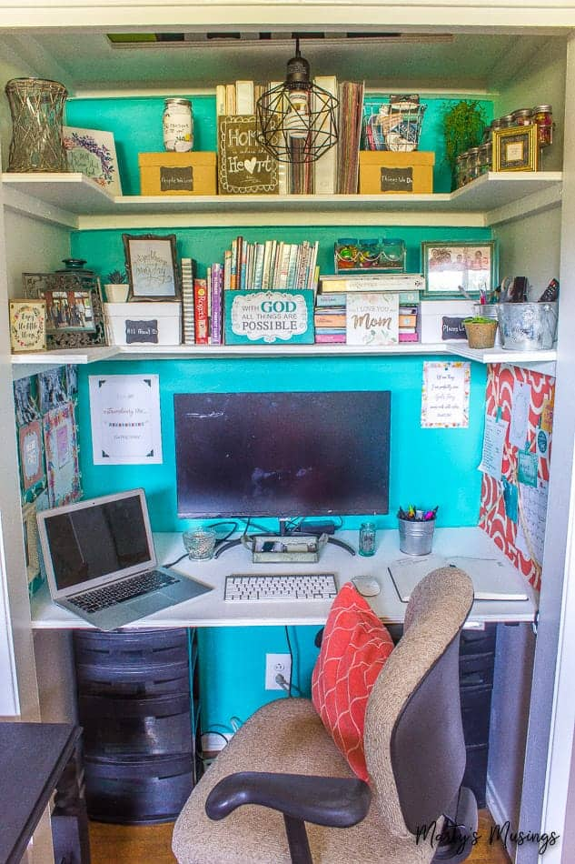 home office in a closet with teal accent wall and shelves