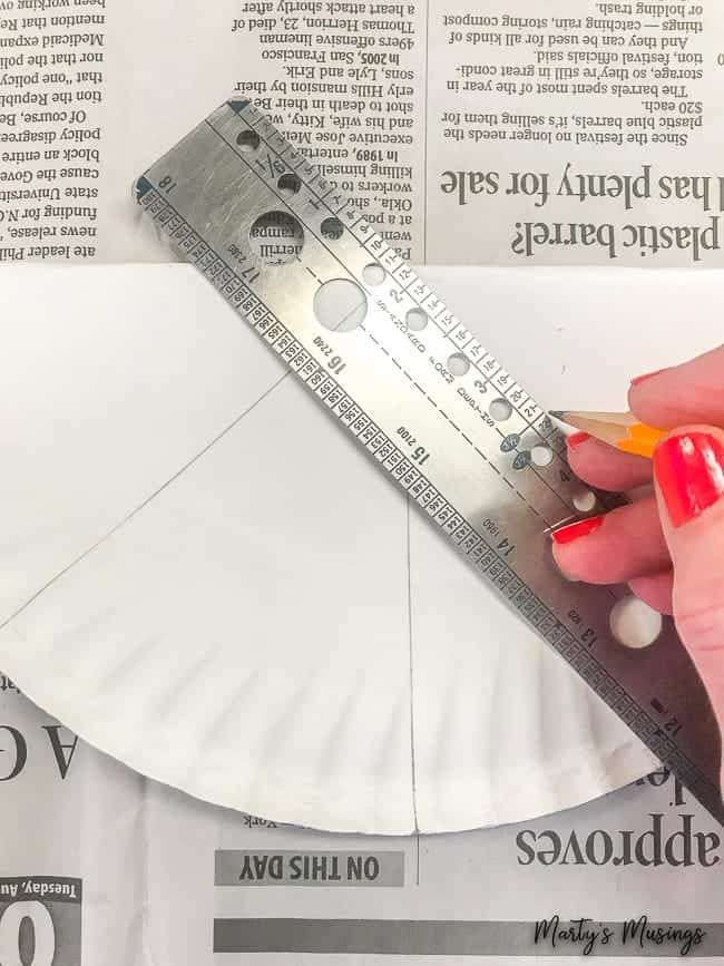 trace lines on folded paper plate with ruler and pencil