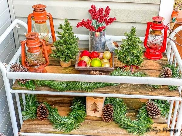 DIY garden cart decorated with greenery and lanterns