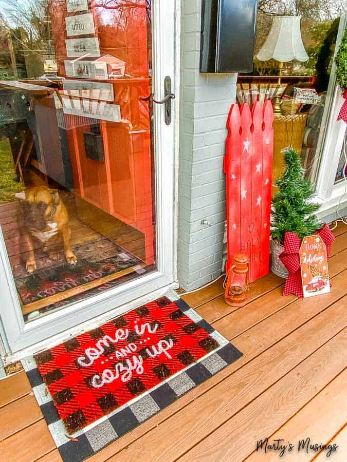 buffalo check layered rugs and Christmas decorations by front door