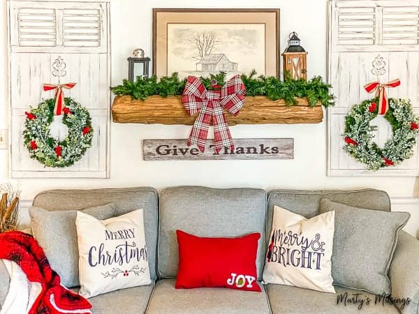 rustic wood mantel with greener and red plaid bow for Christmas