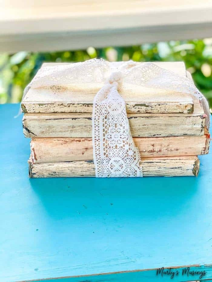 Old books chalk painted and distressed and tied with white lace ribbon
