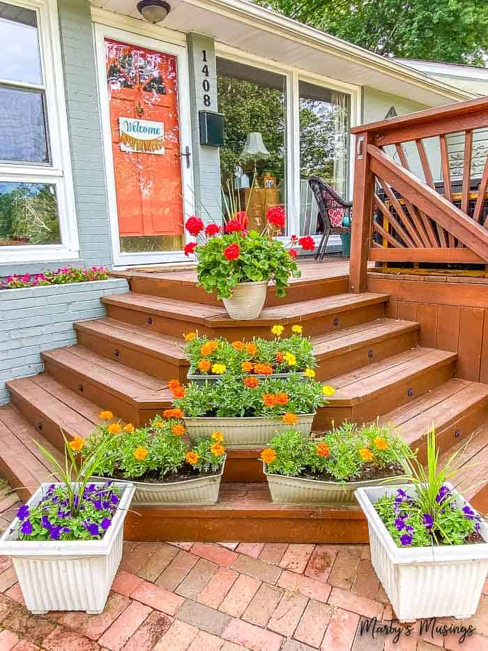 front deck of ranch home decorated with planters full of flowers