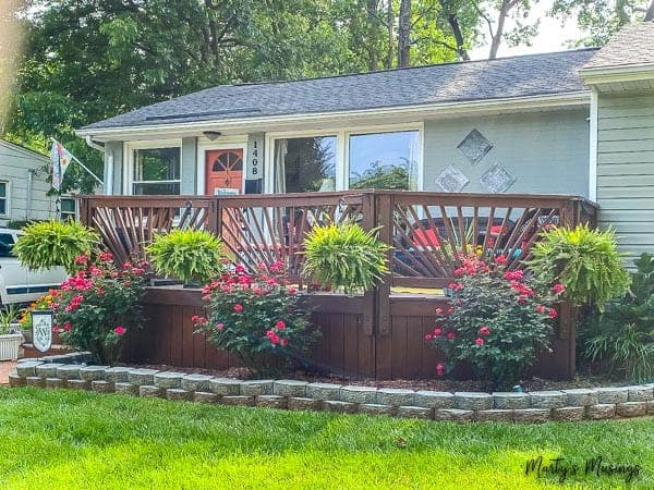 ranch home with front deck decorated with ferns and roses