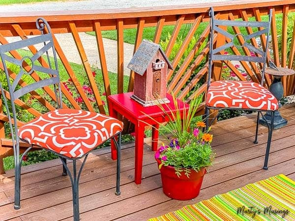 metal chairs with orange fabric and red table with flowers