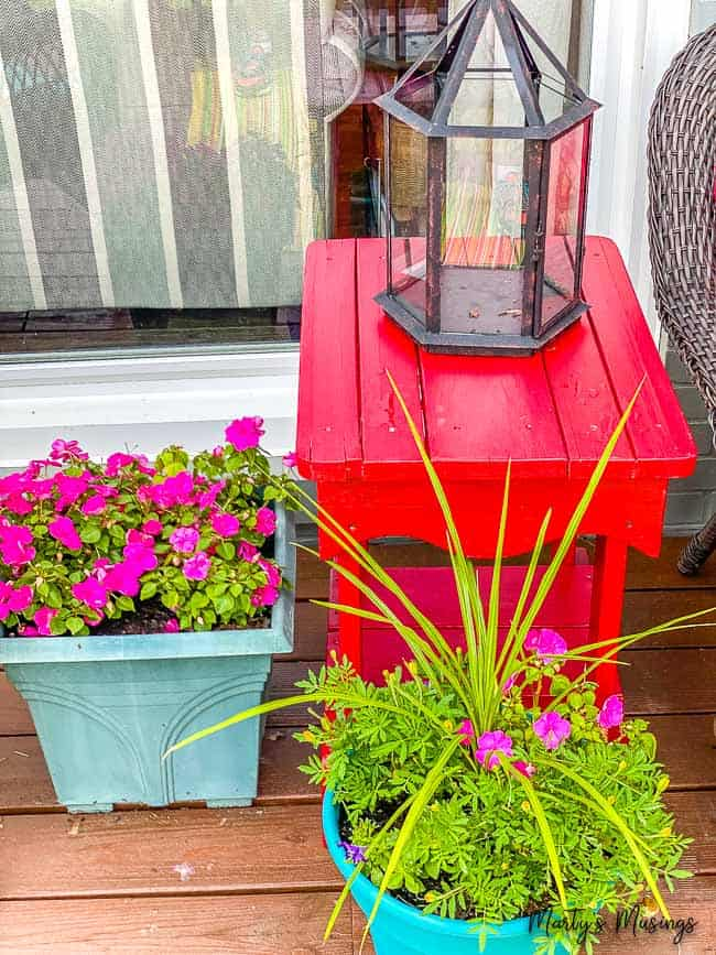 red porch table with planters of flowers