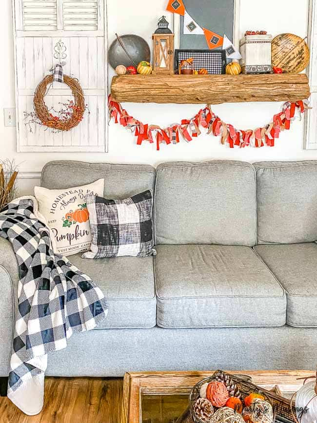 Blue couch with buffalo check accessories for fall