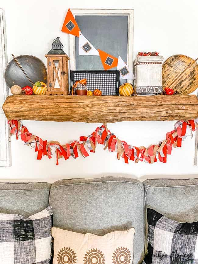 Wood mantel with fall decorations and rag banner