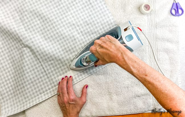 Attach adhesive to buffalo plaid fabric with iron