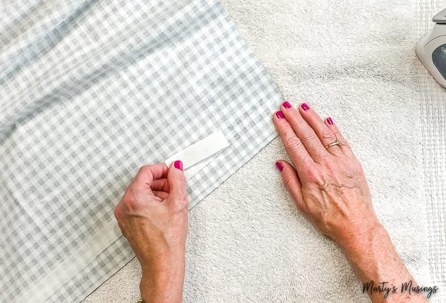 Remove paper from tape adhesive on fabric.