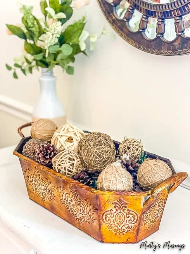 copper container with seasonal elements like pine cones and textured balls
