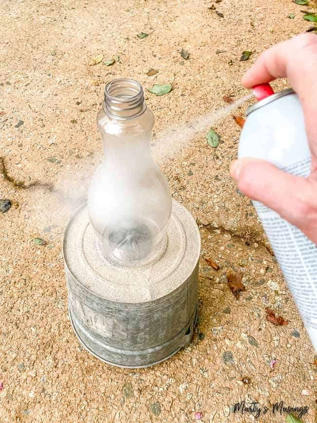 spray paint white a plastic bottle outdoors