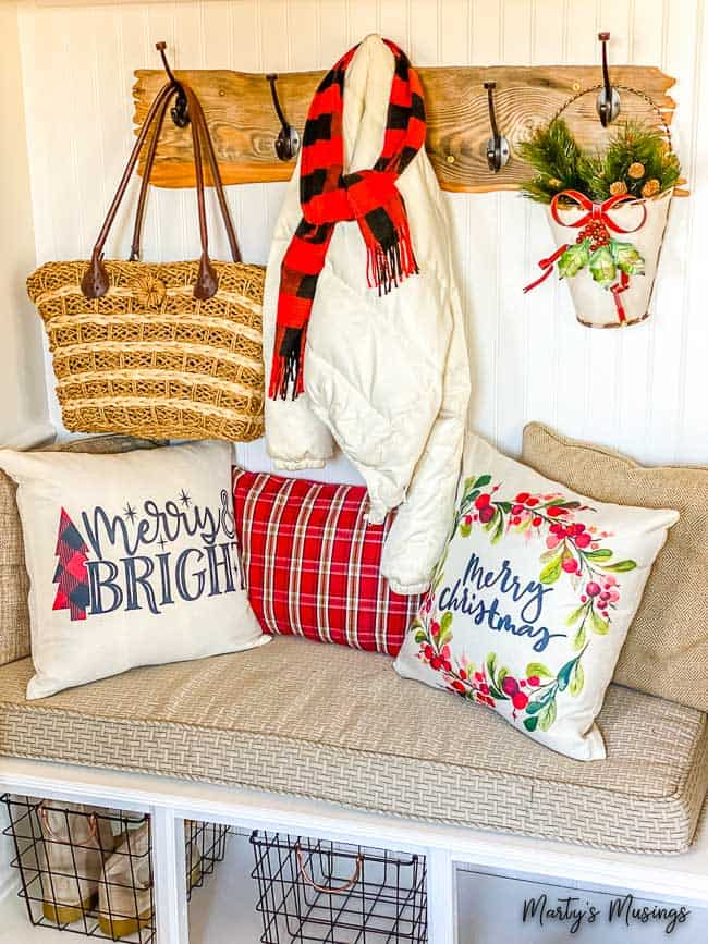 drop zone filled with rustic coat rack, a coat and red buffalo check scarf with Christmas pillows
