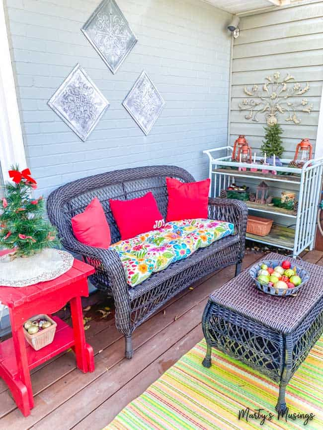 front porch Christmas decorations include red accents with greenery and ornaments