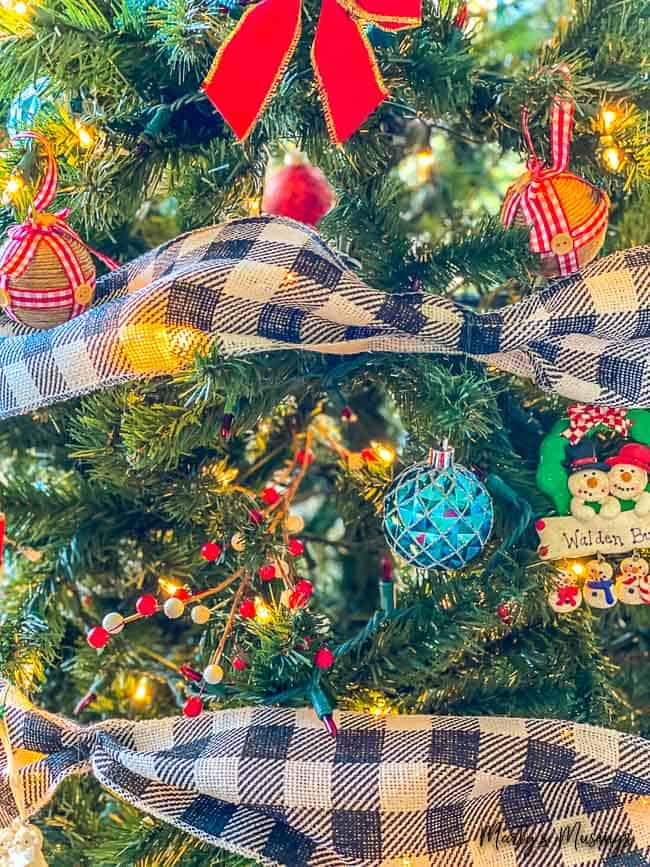 closeup of Christmas tree decorated with black and white checked ribbon and red and blue accents