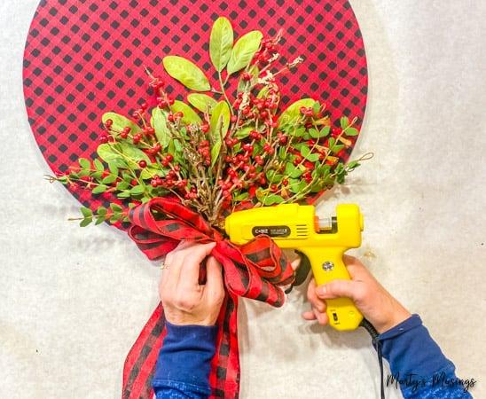 hot glue buffalo plaid bow to DIY wood hoop wreath